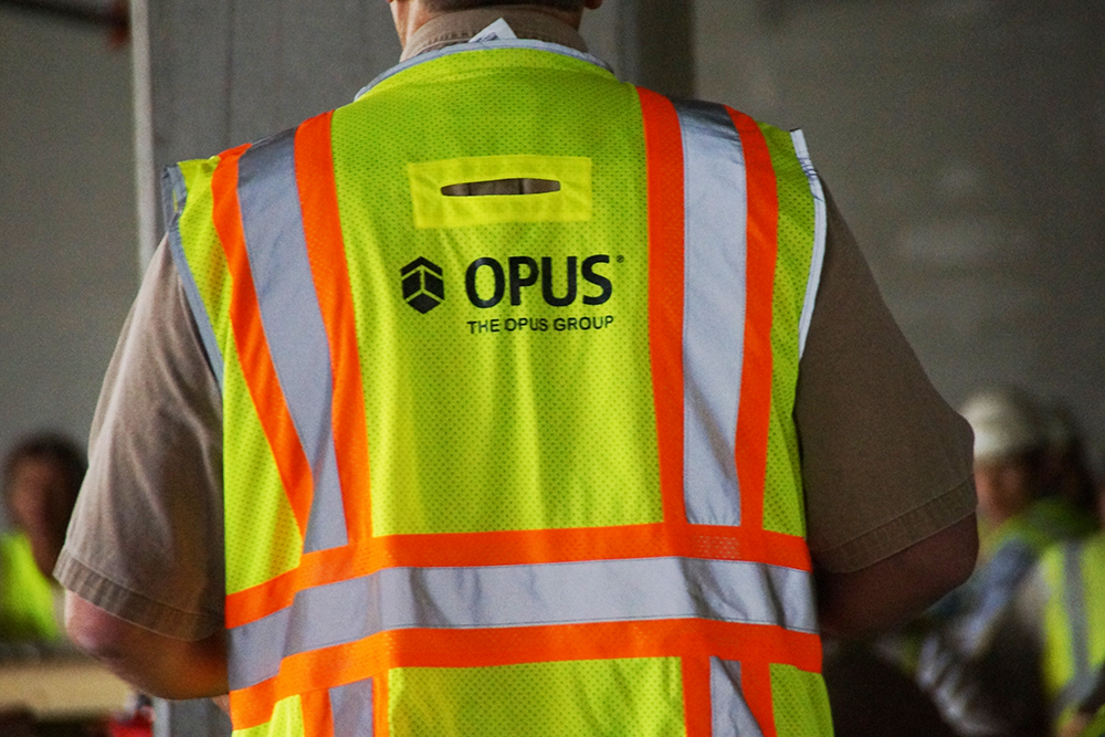 construction worker onsite wearing a high-visibility safety vest with The Opus Group logo