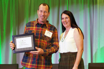Greg Swanson receives his Shining Star volunteer award from Rebuilding Together Twin Cities Executive Director Kathy Greiner