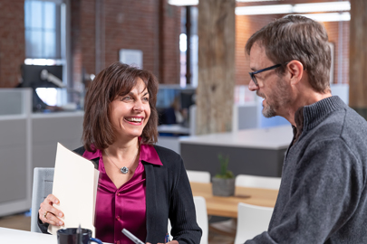 a man and a woman laugh as they collaborate on work