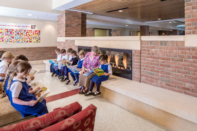 a teacher and young elementary students read in the Heart gathering area of Visitation School in Mendota Heights, Minnesota