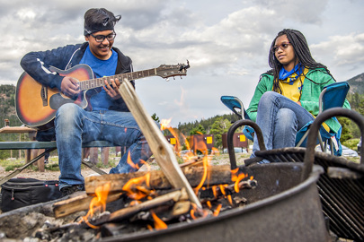 Boy with guitar and girl sitting around campfire
