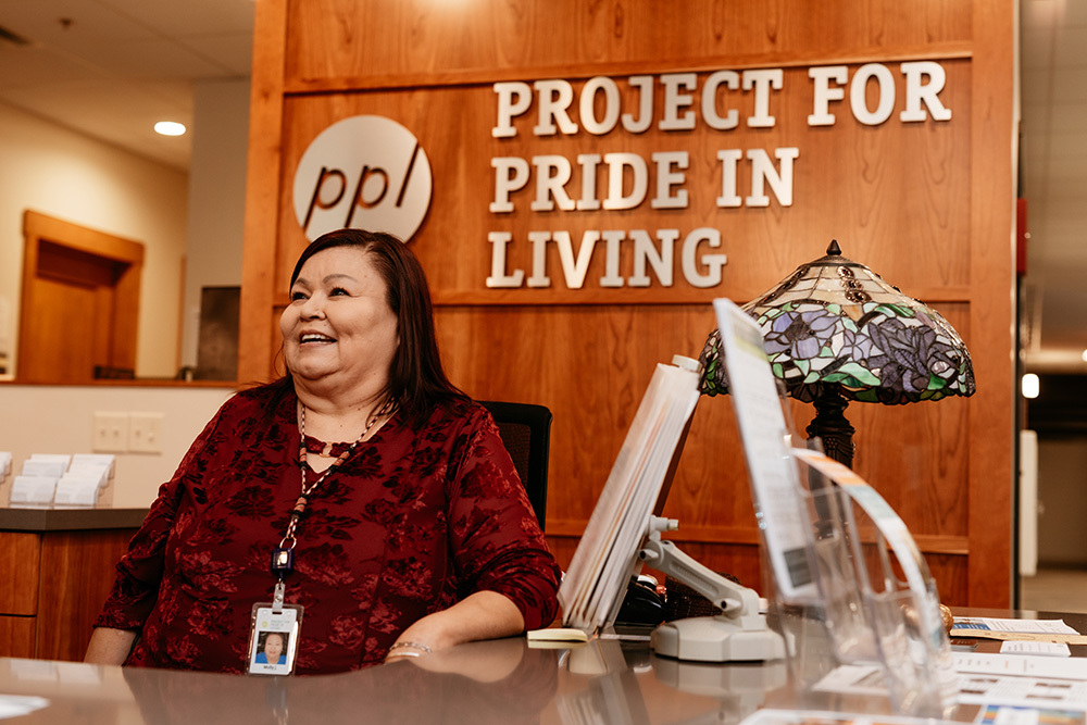 Woman at Project for Pride in Living desk