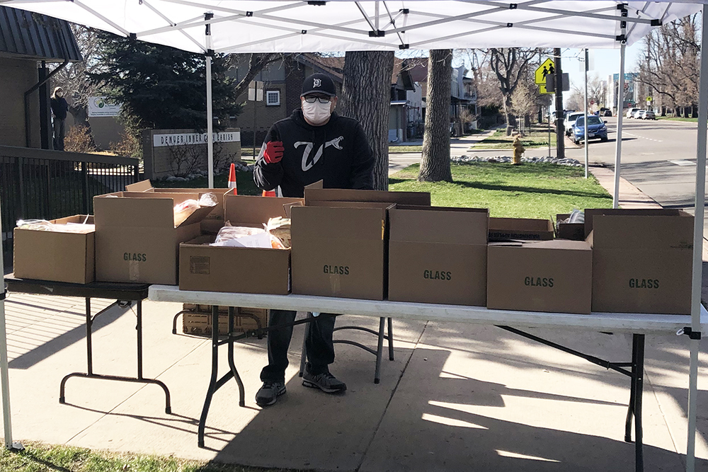 Man standing outside by table with boxes